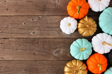 Autumn side border of various colorful pumpkins on a rustic wood background. Top view with copy space.