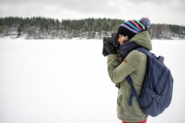 A woman photographer in warm clothes and a backpack is holding a camera in her hands and taking pictures of a winter landscape. Against the backdrop of lakes, cliffs and forests of the cold winter.