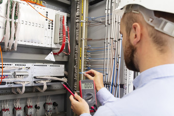Engineer electrician with multimeter in electrical control box tests equipment. Maintenance of electrical panel. Worker in helmet in power supply cabinet. Service man is testing automation fuse box