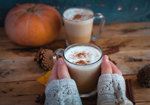 Close-up of hand holding pumpkin spice latte in glass cup on wooden background