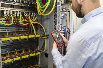 Electrician engineer testing cabling connection of high voltage power electric line in industrial distribution fuse board. Service man with multimeter. Tester in hands of electric worker.