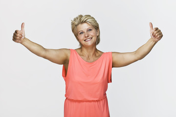 Smiling blonde woman giving thumbs ups. Isolated on white background