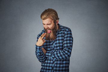 disgusted man with finger in mouth displeased wants to throw up