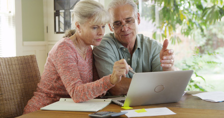 Senior couple using laptop computer to pay bills