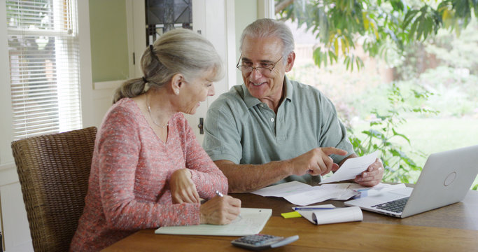 Senior couple paying bills together on laptop