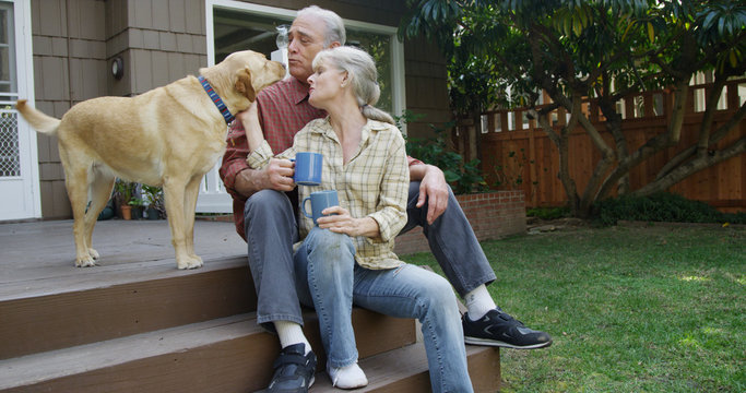 Senior couple having coffee petting dog in their yard