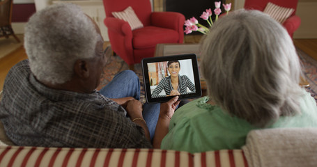 Happy senior black couple video chatting with granddaughter