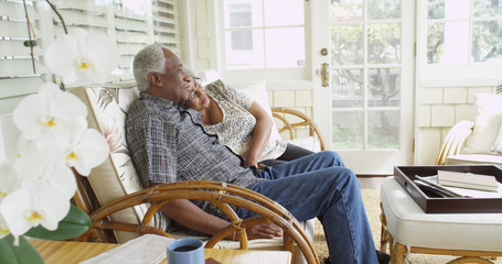Happy elderly African couple sitting on a couch