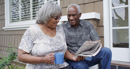 Happy retired African American couple reading newspaper