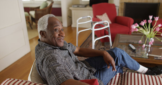 Retired African man relaxed and talking on his couch