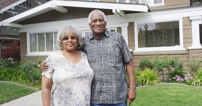 Happy elderly black couple standing on front yard
