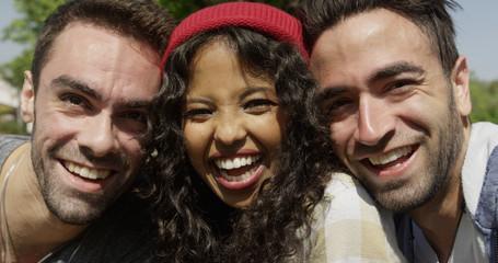 Closeup of three young multiracial friends enjoying the sun