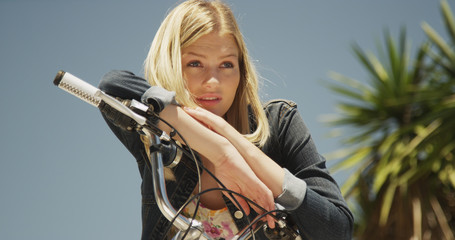 Youthful white woman sitting on a bicycle outdoors