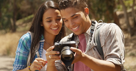 Happy young backpacking couple with camera looking at pictures
