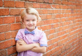 Cute Young Caucasian Boy Portrait Against A Brick Wall