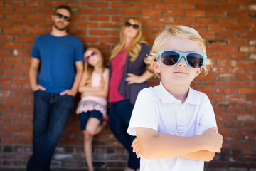 Cute Young Caucasian Boy Wearing Sunglasses with Family Behind