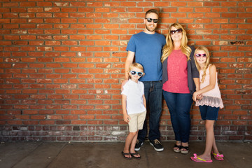 Young Caucasian Family Wearing Sunglasses Against Brick Wall