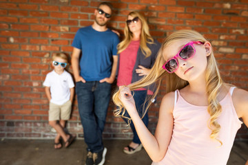 Cute Young Caucasian Girl Wearing Sunglasses with Family Behind