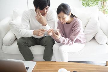夫婦が、スマートフォンを操作しながら、話し合っている。