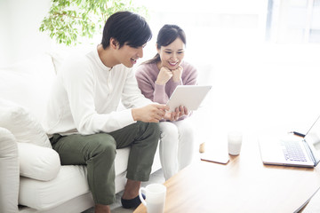 タブレットを見ながら、楽しそうに話をしているカップル。