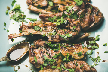 Meat dinner. Grilled lamb ribs with green parsley and sauce in blue serving plate over concrete table background, selective focus, horizontal composition, close-up. Slow comfort food concept