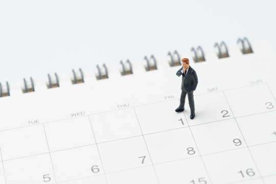 Start or beginning of month for salary man concept, miniature people businessman office guy standing at 1 date on calendar, ready to start new business month