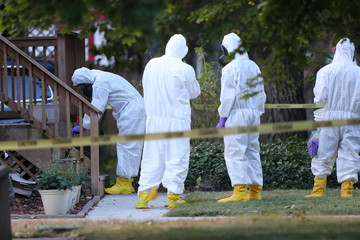 """FBI and law enforcement officers in hazmat suites take pictures and water evidence at a house which FBI says was investigating """"potentially hazardous chemicals"""" in Logan"""