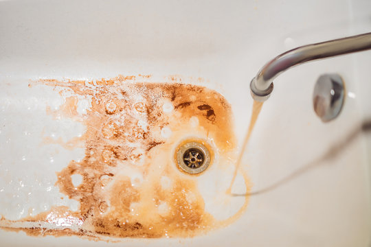 Dirty brown running water falling into a white sink from tap. Environmental pollution concept