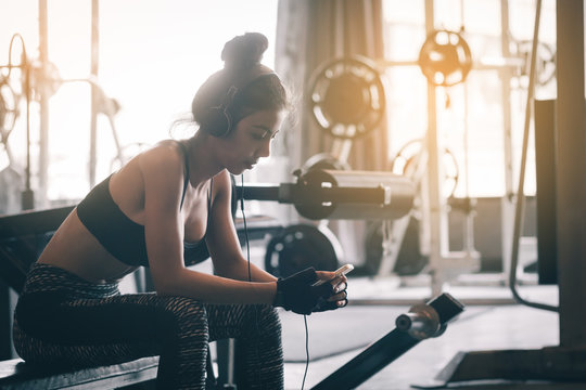 Healthy asian woman relaxing and exercise with listen music after the workout at gym.