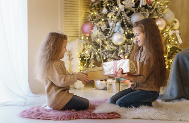 Two little sisters are waiting for Christmas. Girls are sitting by Christmas tree, smiling and exchanging presents. They are dressed in jeans and sweaters. Happy childhood.
