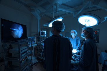 group of veterinarian surgery in operation room take with art lighting and blue filter