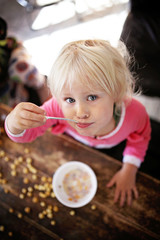 Cute Toddler Girl Eating Breakfast Cereal on a Sunny Morning