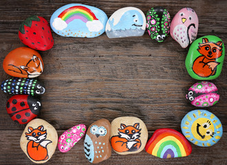Border of Colorful Cartoon Hand Painted Animal Rocks on Wood Background