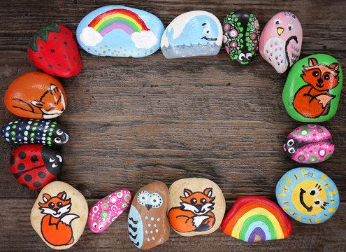 Border of Colorful Cartoon Hand Painted Animal Rocks on Wood Background