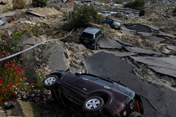 Cars as seen on a broken road after an earthquake hit Balaroa sub-district in Palu