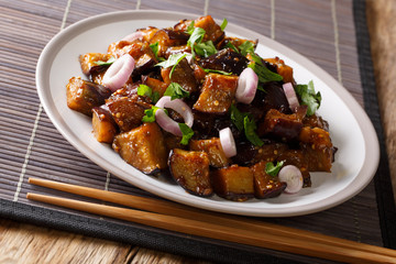 Sichuan Style Braised Eggplant With ginger, garlic, pepper and suy sauce closeup on a plate. Horizontal