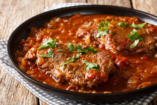 Juicy cube Swiss steak fried and slowly stewed in a spicy tomato sauce with vegetables close-up. horizontal