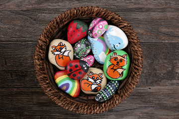 Collection of Hand Painted Colorful Cartoon Rocks in w Wicker Basket Wall mural
