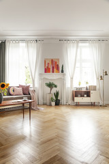 Poster, plants and cupboard in bright loft interior with wooden floor and drapes at windows. Real photo