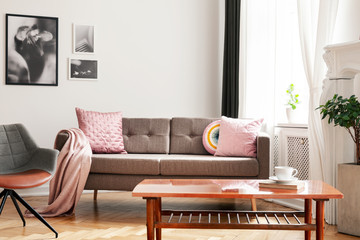 Pink pillows on sofa next to armchair in white living room interior with posters and table. Real photo