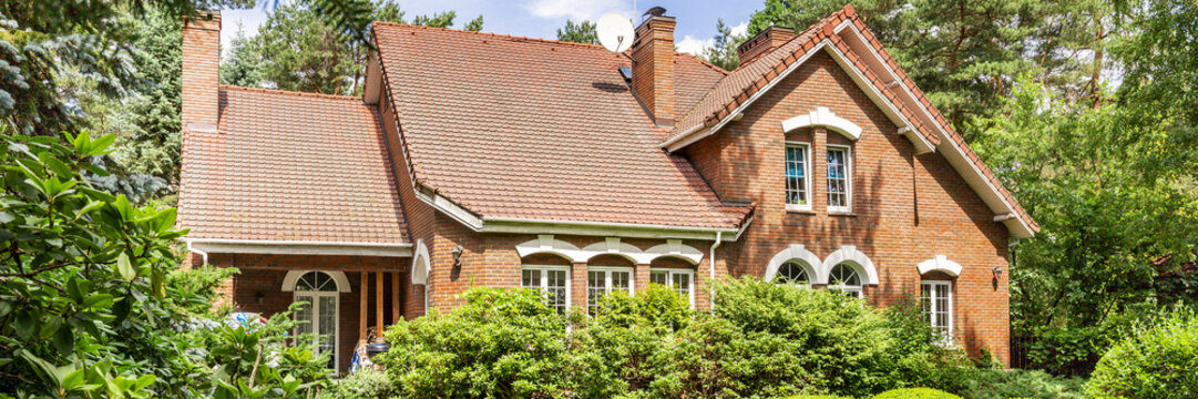 A red brick English style classic house with a steep roof and large windows surrounded by trees and green plants. Panorama.