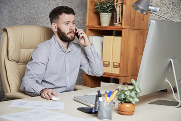 Concerned business executive talking on phone and reading data on computer screen