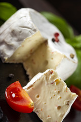 Camembert cheese with cherry tomatoes on a dark slate