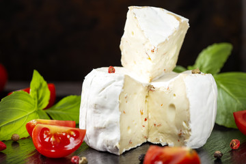 Camembert cheese with cherry tomatoes and basil leaves on a dark slate