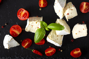 Pieces of camembert cheese with cherry tomatoes and basil leaves