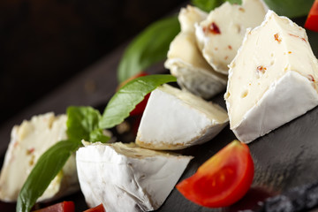 Pieces of camembert cheese with cherry tomatoes and basil leaves on a dark slate