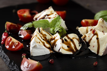 Pieces of camembert cheese with cherry tomatoes balsamic vinegar on a dark slate