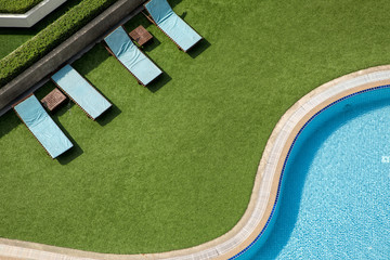 Close up outdoor swimming pool and pool chairs with clear clean water