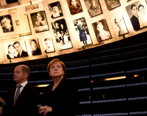 German Chancellor Angela Merkel looks at pictures of Jews killed in the Holocaust during a visit to the Hall of Names in the Holocaust History Museum at the Yad Vashem World Holocaust Remembrance Center in Jerusalem