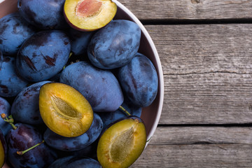 Fresh plums in bowl on wooden table